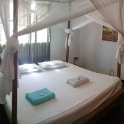 Large double bed in hotel room with clean towels and mosquitos net at Ten Degrees South Lodge in mikindani mtwara tanzania