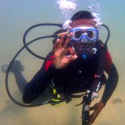 Happy diver man underwater doing ok sign in sandy area at Eco2 Diving mtwara south tanzania