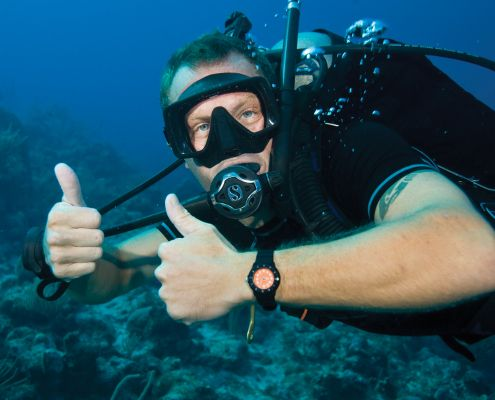 Portrait of happy beginner diver underwater with thumbs up geared with full equipment at PADI eco2 diving Mtwara Tanzania
