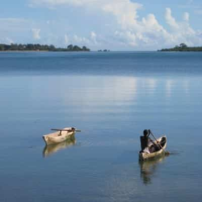 Traditional swahili fisherman paddling on a canoe in mikindani bay mtwara tanzania with a second empty canoe on his left