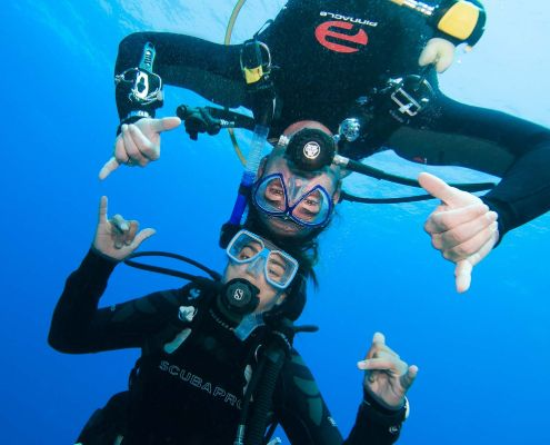 Two happy scuba divers underwater head to head in the blue during PADI Courses at Eco2 Diving Mtwara Tanzania